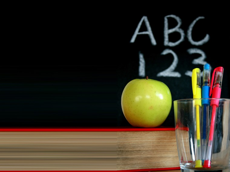 Chalkboard with a green apple and pens backgrounds