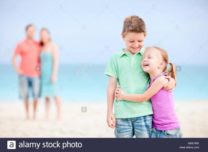 Brother and sister embracing each other while parents standing on