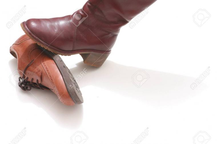 Domination Symbolized By Shoes On White Background Stock Photo