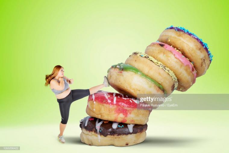 Overweight Woman Kicking Donuts Over White Background Stock Photo