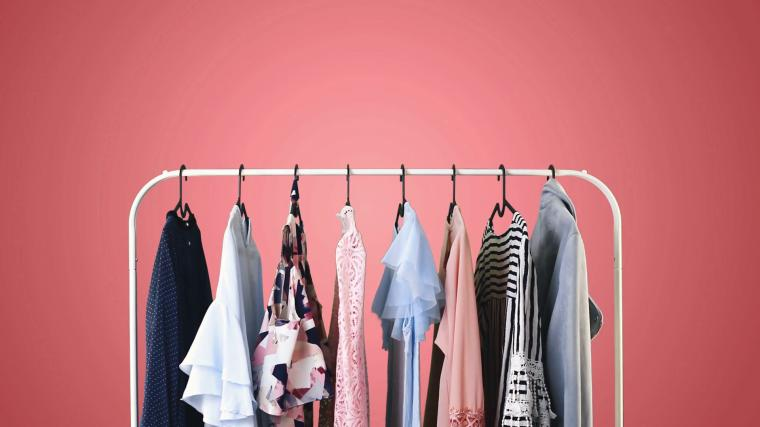 Womens clothing on a white clothes hanger on pink pastel