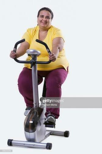Portrait Of An Overweight Woman Exercising Over White Background