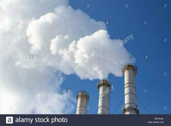 Smoking pipes making clouds against blue sky background Dioxide