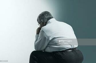 Rear View Of Overweight Mature Man Sitting Against Blue Background