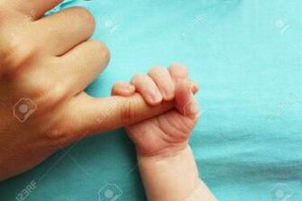 Small Baby Holding Parents Hand On Blue Background Stock Photo