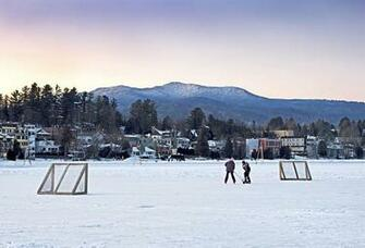 Kids Playing Hockey On Mirror Lake With Lake Placid Village Shown