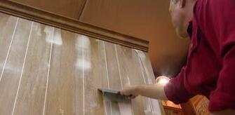 Smoothing out joint compound in paneling grooves with a drywall knife