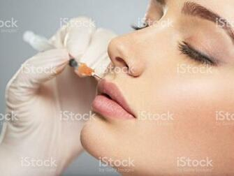 Young Woman Gets Botox Injection In Her Lips Stock Photo