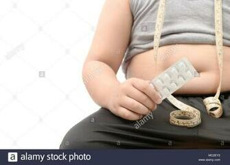 Overweight fat boy with obese belly taking slimming pills isolated