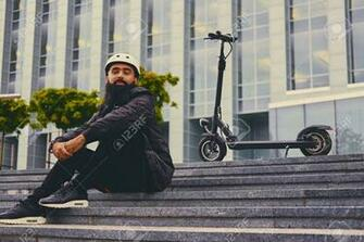 Stylish Bearded Male On A Step Over Electric Scooter Background