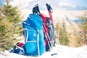 Two Backpacks In The Background Of Snow capped Mountains And