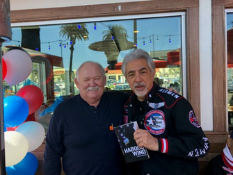 Joe Mantegna receives an autographed copy of Tommy Andersons